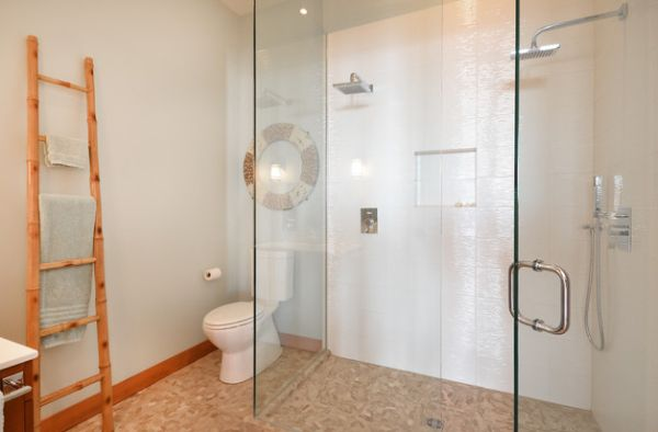 Lovely modern bathroom uses natural tones and glass shower space to create a refreshing feel