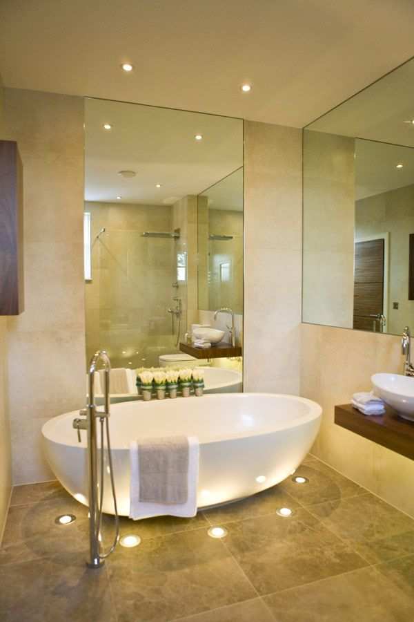 Lights in the floor surround this contemporary tub, creating a relaxing atmosphere.