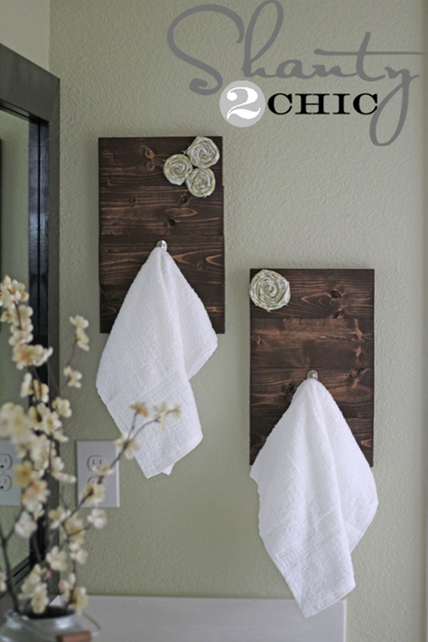 Dark wood towel hooks with fabric rosettes