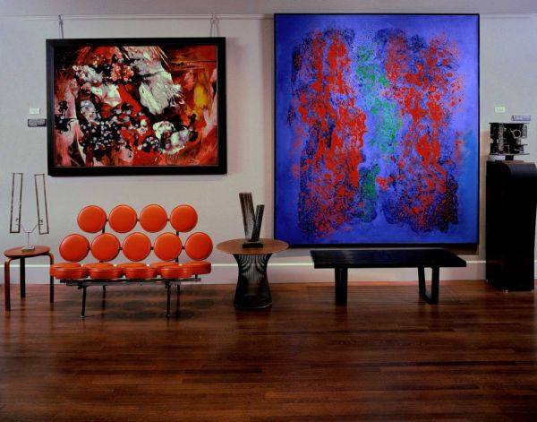 Marshmallow Sofa in bright orange flanked by interesting art work