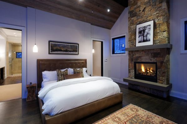 Wooden ceiling and stone fireplace give the bedroom a luxury cabin appeal