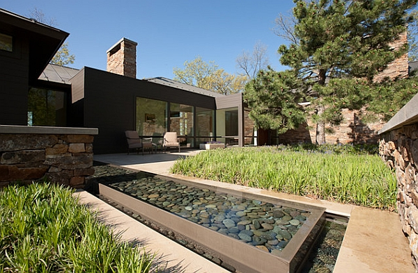 Small reflective pool in the backyard with rounded cobbles
