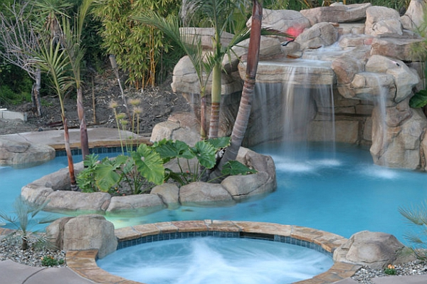 A hot tub and waterfall feature add to the grandeur of your backyard pool