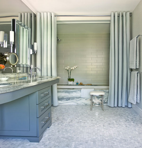 Shower curtains in solid color complement the marble tub