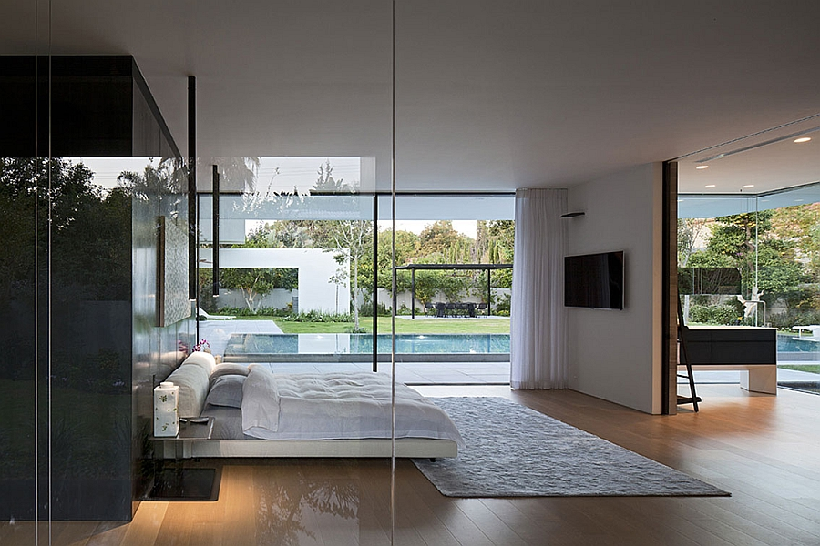 Frameless glass walls and doors connect the bedroom with the courtyards