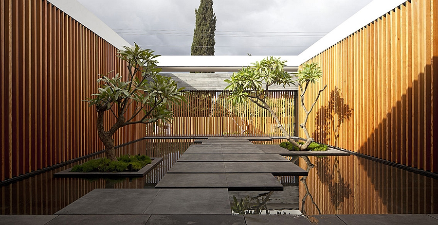 Stunning entryway idea with wooden slats, reflective pools and basalt rock