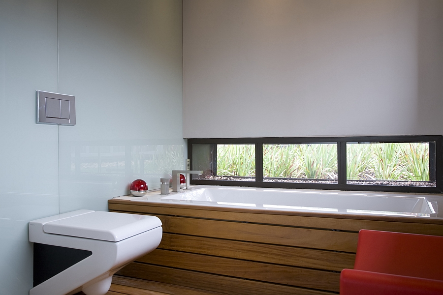 Stylish bathroom in white with red and wooden accents