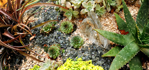 Pebbles, glass and low maintenance plants create a serene scape