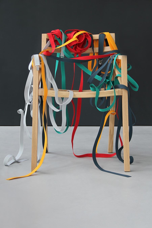 Loose suspender straps around teh frame of the Bretelle Chair