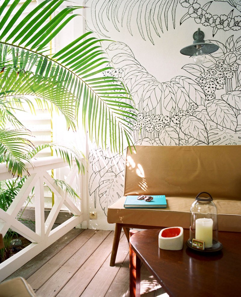 Sitting area with a wall mural and tropical greenery