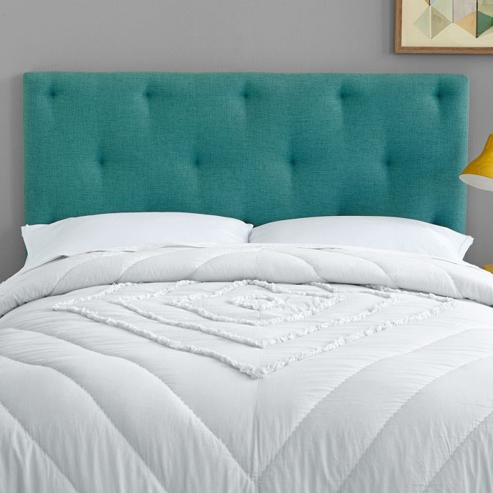Teal tufted headboard meets a gold reading lamp