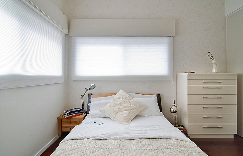 Wallpaper adds subtle elegance to the soothing master bedroom in the small apartment