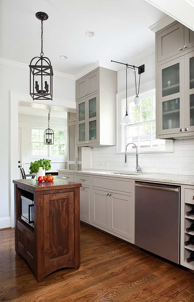Transitional kitchen with a tiny island and beautiful lighting [Design: TerraCotta Studio]