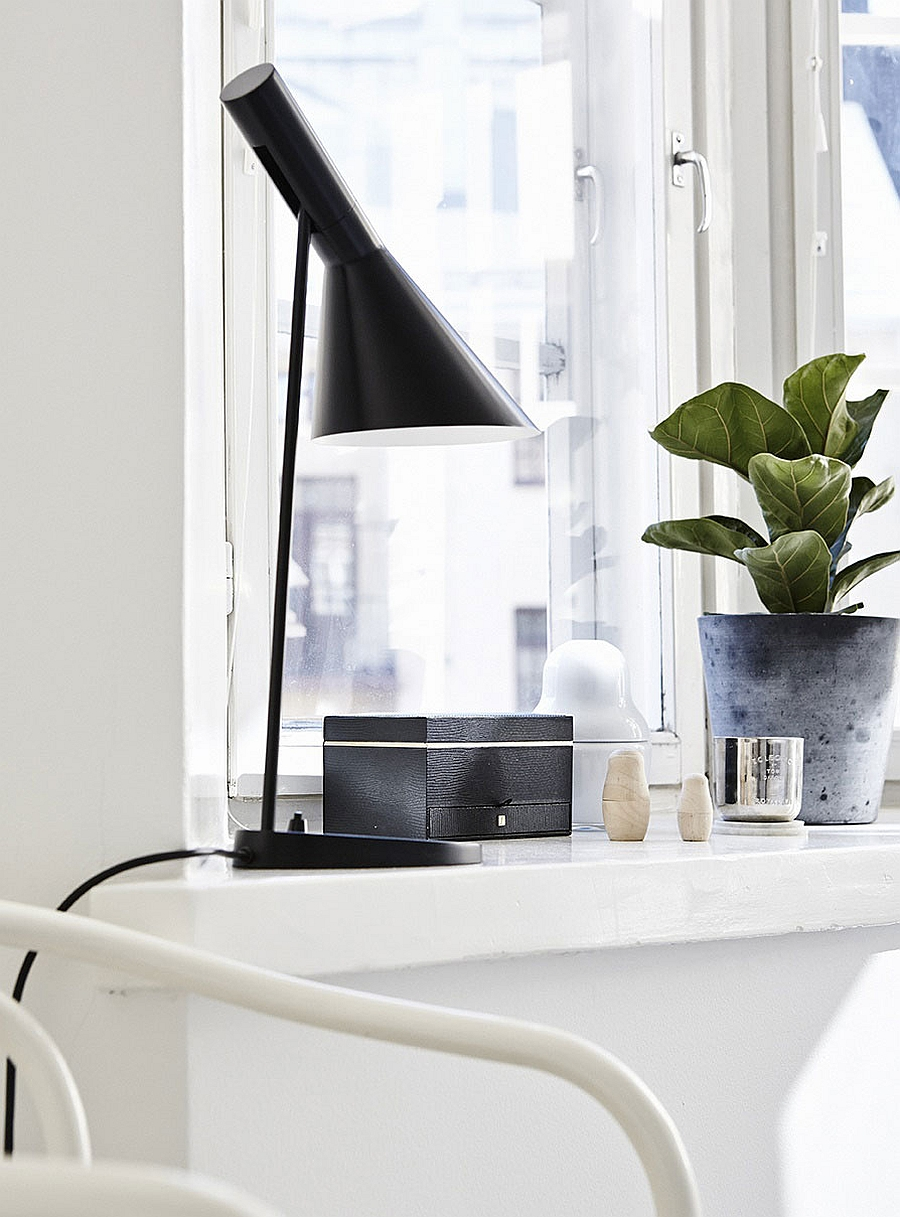 Dark bedside lamp stands out thanks to the all-white bedroom backdrop