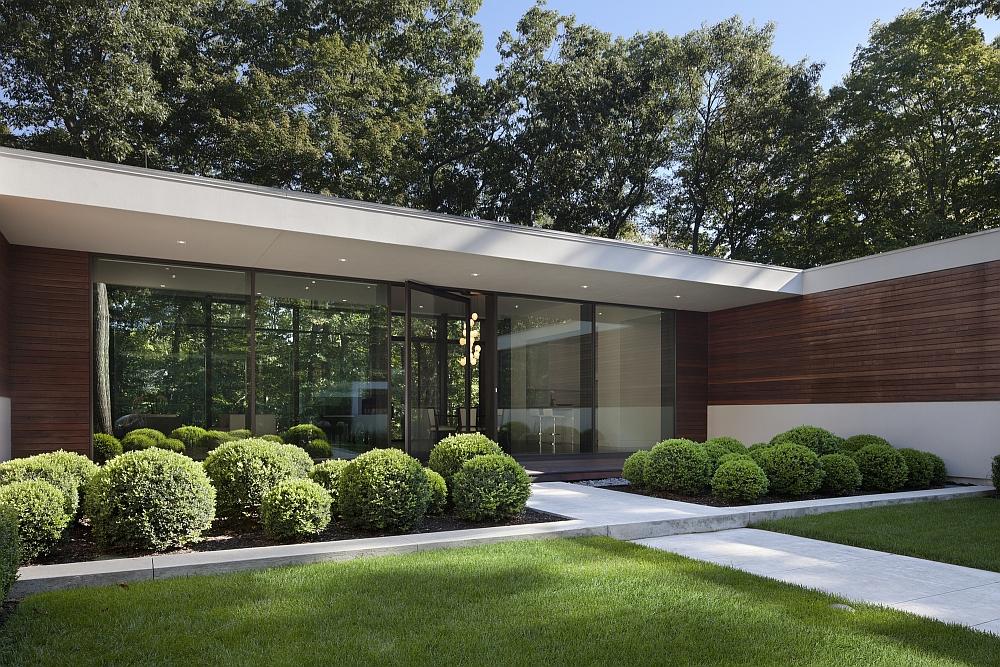 Large glass windows take the greenery inside the house visually