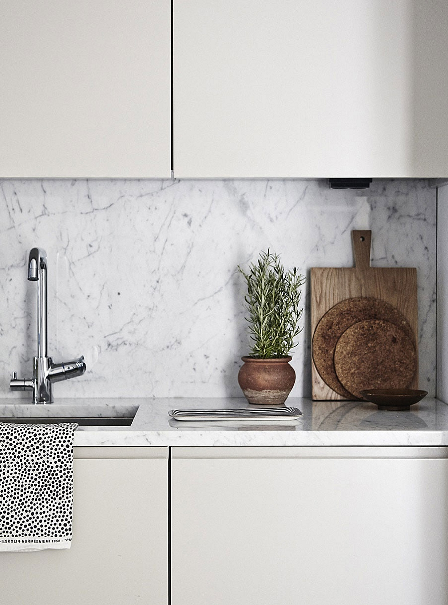 Marble backsplash in the kitchen adds elegance to the Scandinavian design