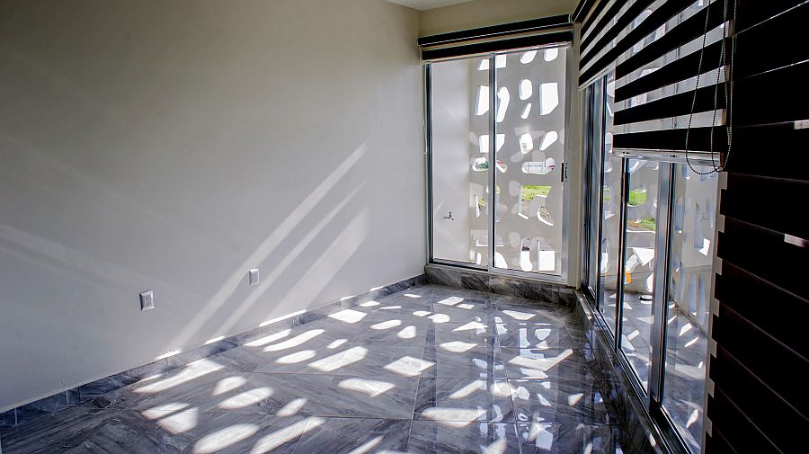 Perforated concrete screen brings in ventilation even while offering privacy