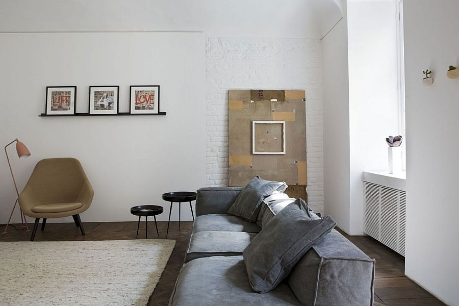 Brick wall adds textural beauty to the black and white living room