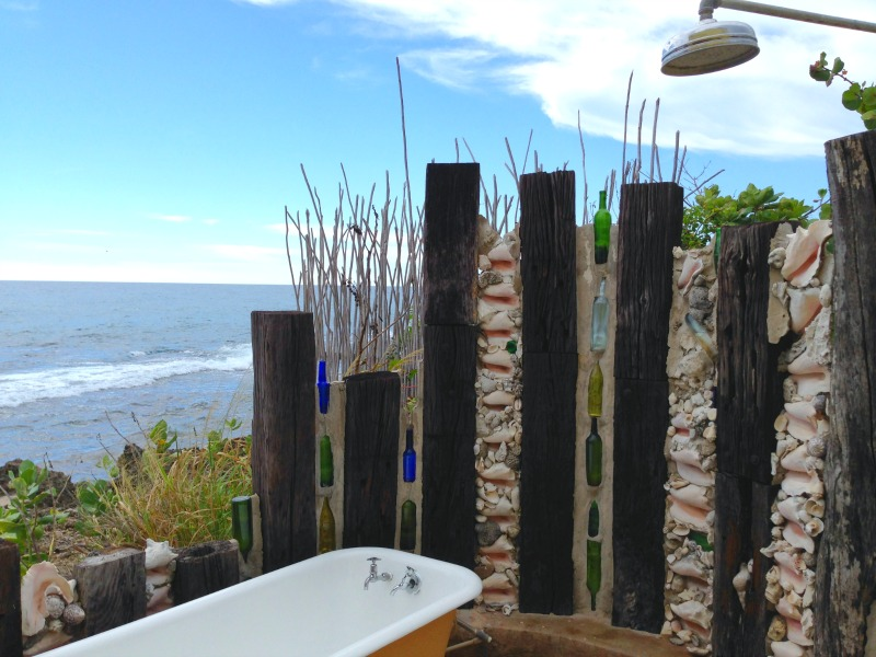 The upcycled bottle wall just makes this outdoor shower perfect