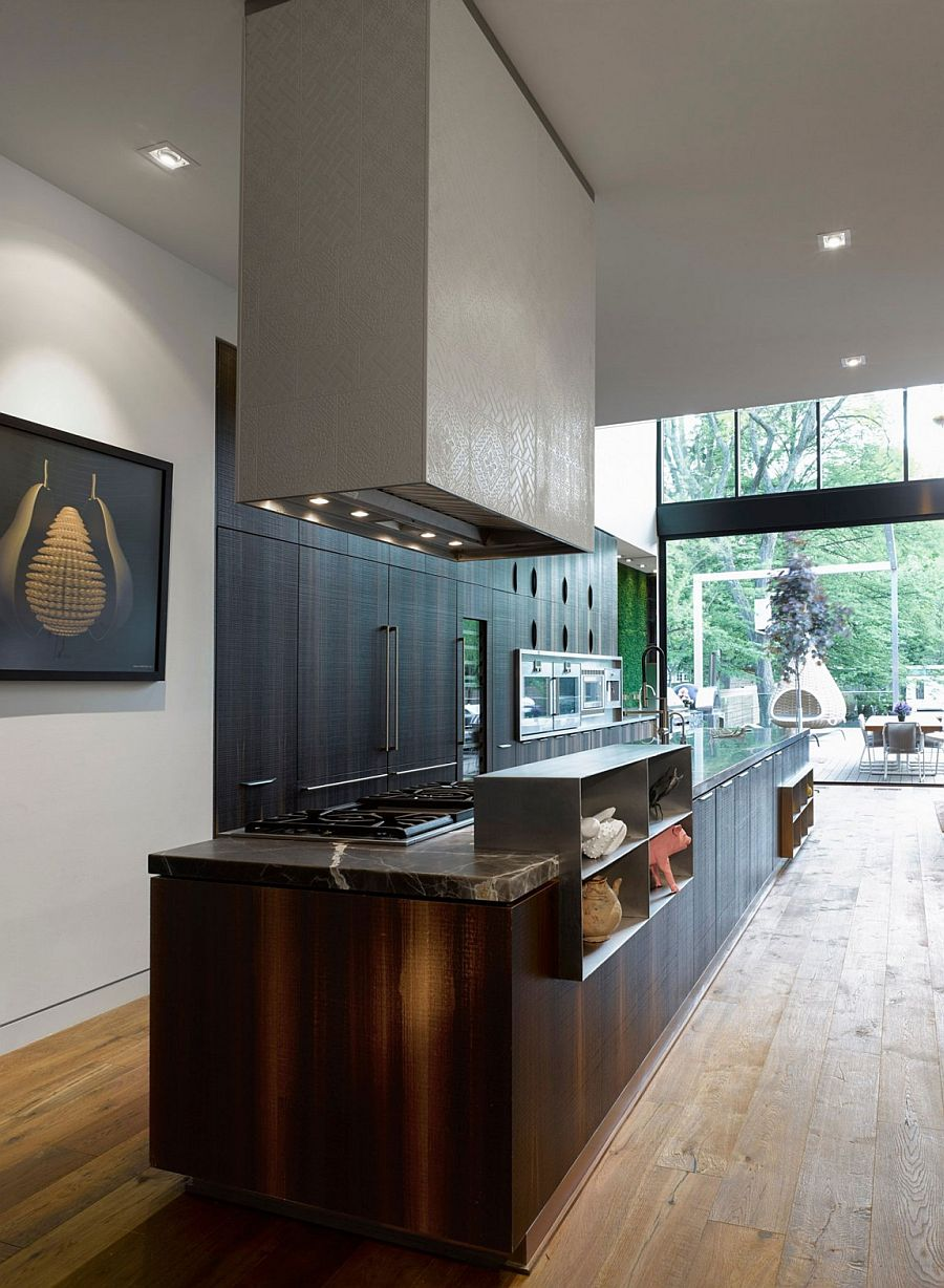 Kitchen island that is seamlessly connected with the deck outside using large glass doors