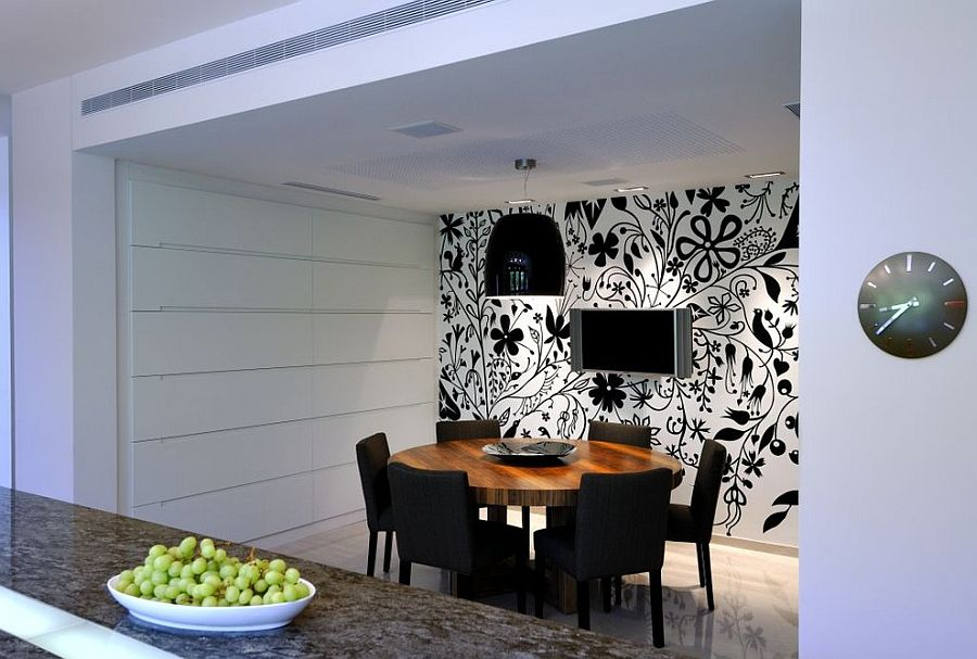 Lighting adds to the appeal of the striking black and white wallpaper in the dining room [Design: Amitzi Architects]