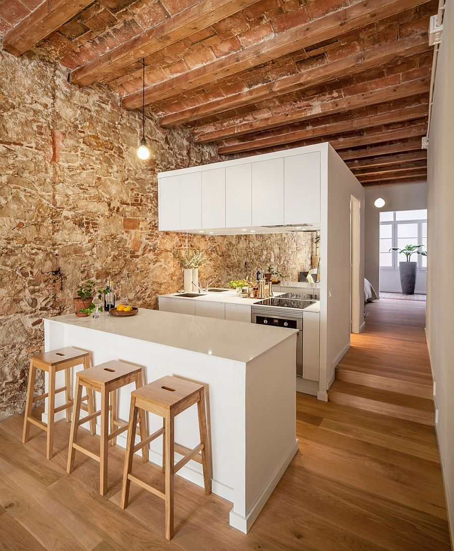 Wooden ceiling beams and stone wall stand in contrast to the sleek white kitchen