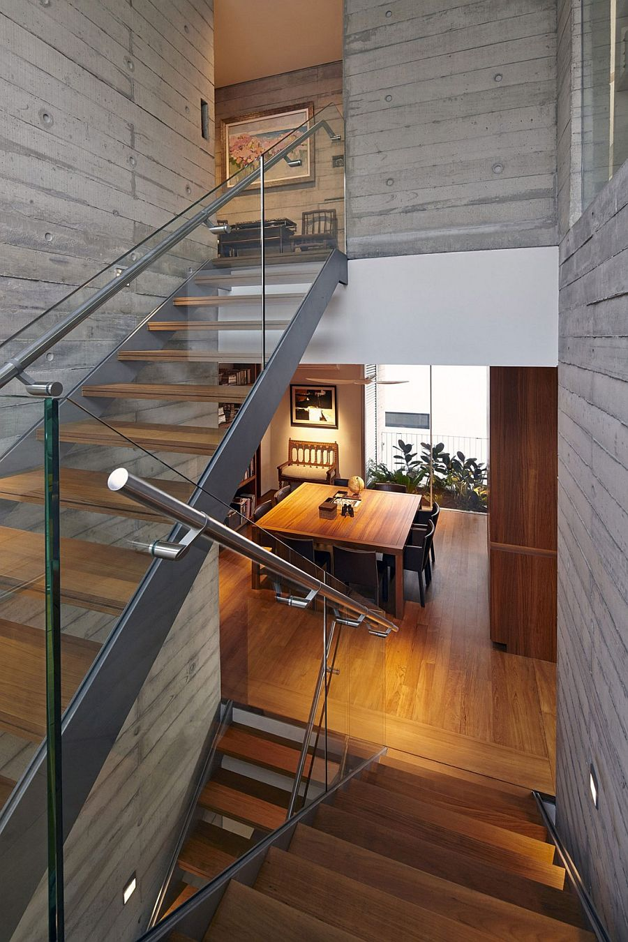 Staircase with wooden steps and glass railing inside the contemporary home