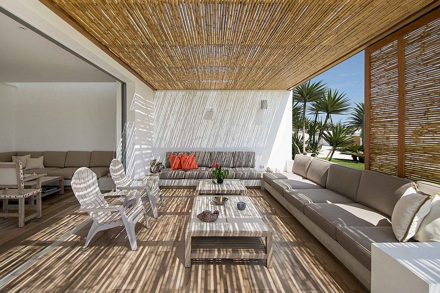 Comfy outdoor lounge area with bamboo blinds and plush seating