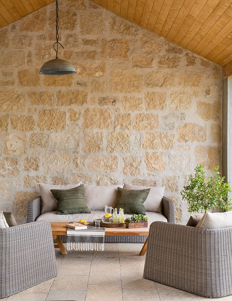 Lovely patio with stone wall and cozy decor