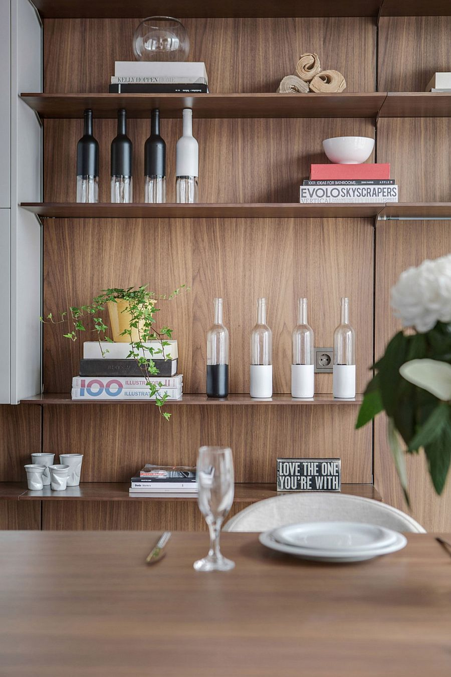 Open floating shelves in the kitchen coupled with minimal white cabinets