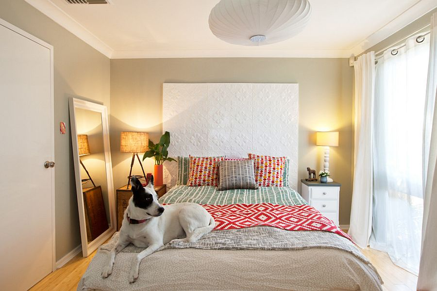 Small bedroom decorating idea with mismatched bedside tables and a mirror