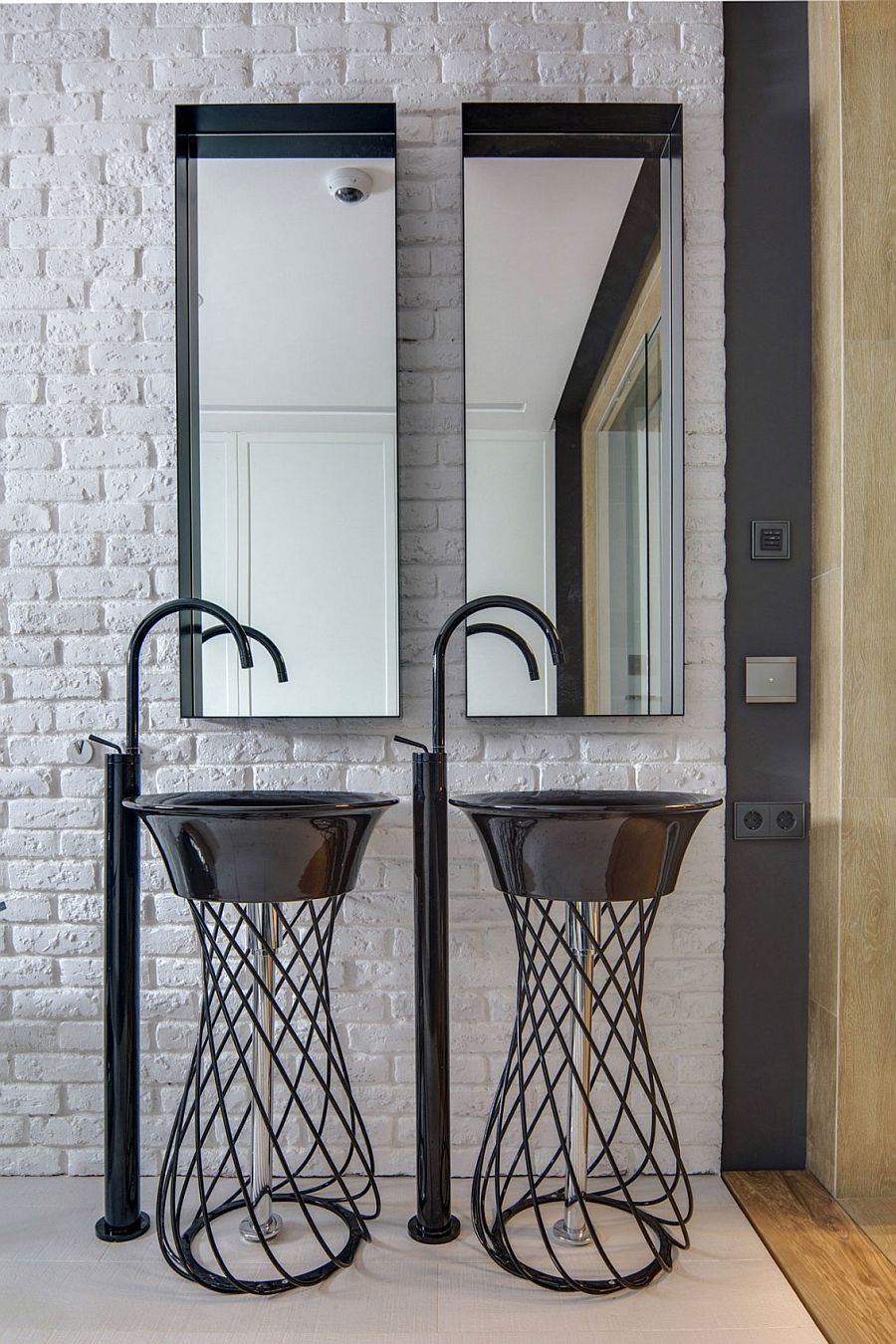 Trendy twin sinks in the bathroom with brick wall