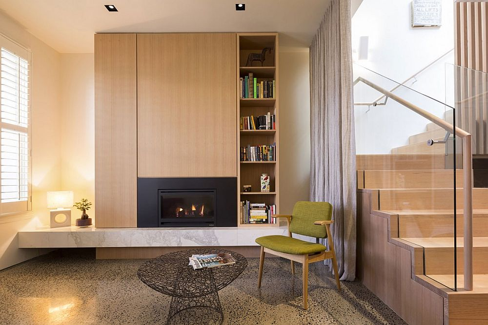 Cozy reading nook idea with accent chair in green and a contemporary fireplace