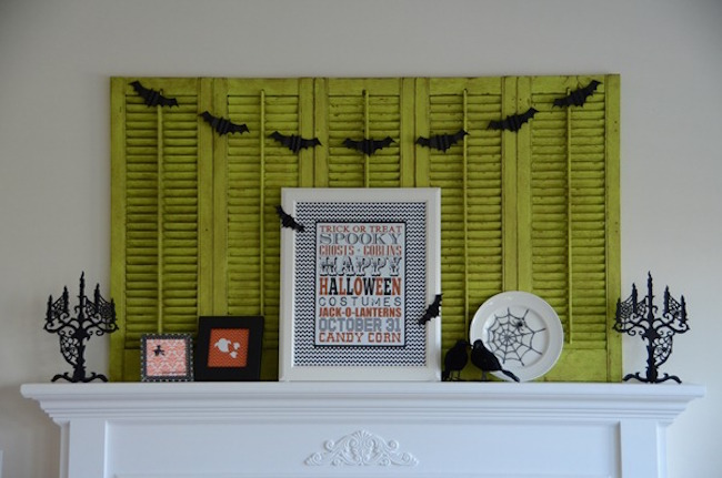 Halloween decorations paired with weathered green shutters on a mantel