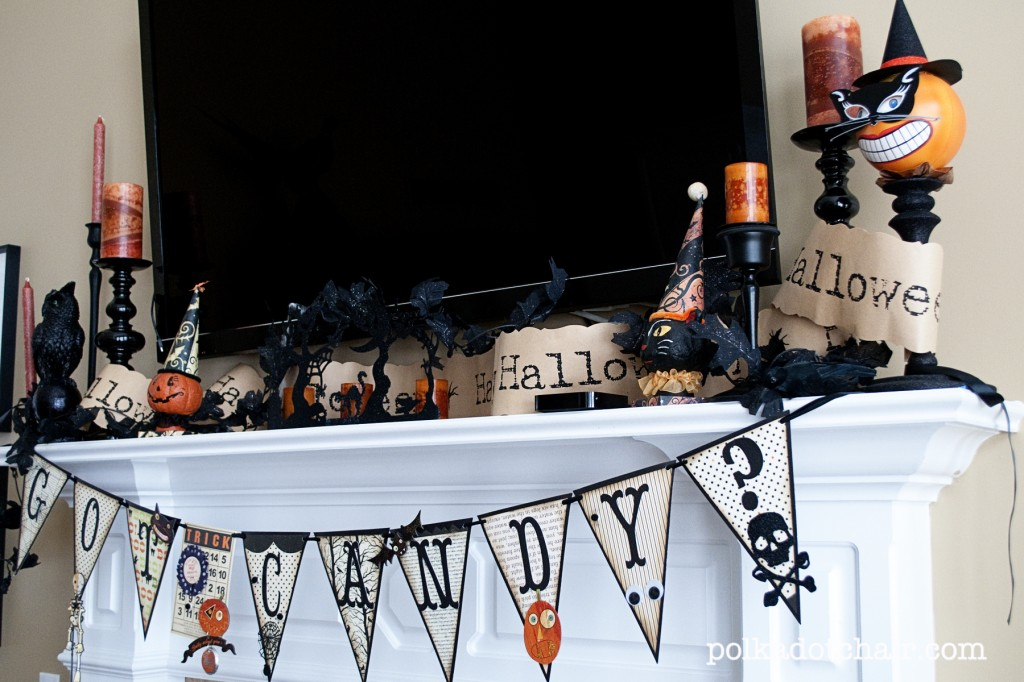 Small Halloween decorations on a mantel with a TV