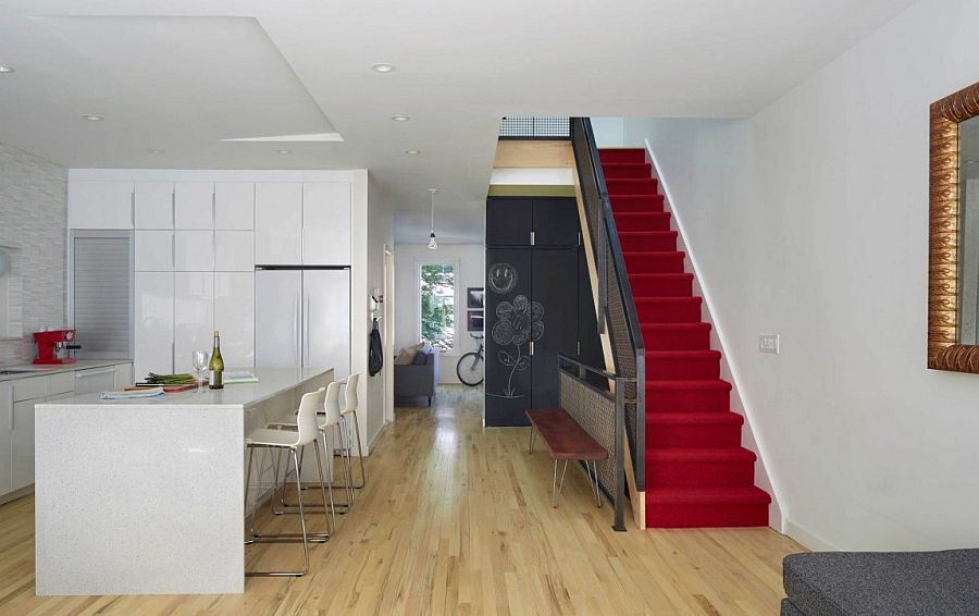 Stairway runner in red and a chalkboard wall provide contrast in the neutral setting