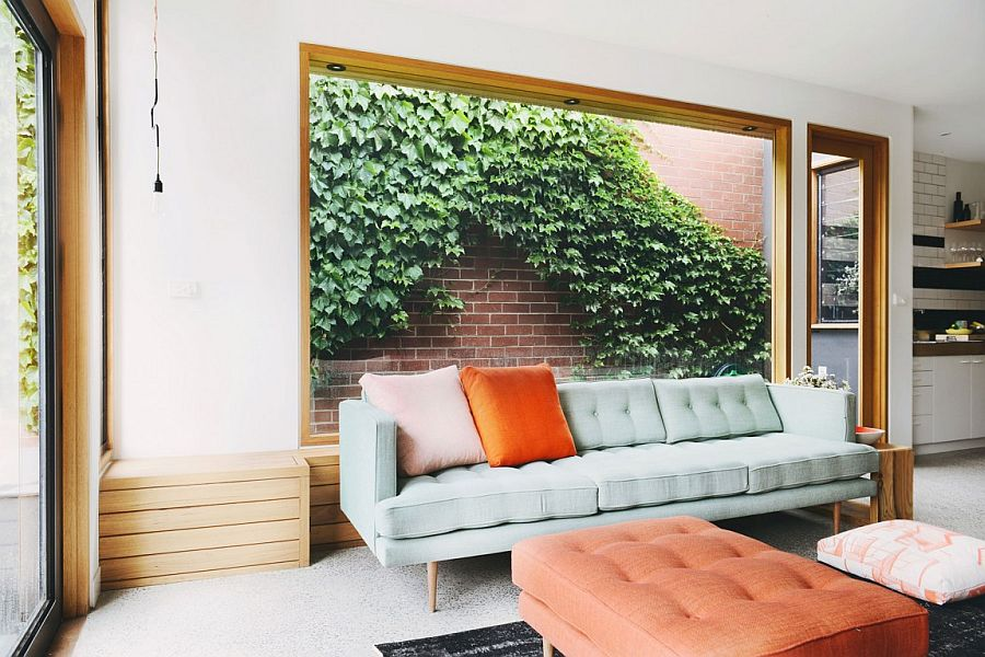 Large wooden bench in the living area with large glass window that looks onto the greenery outside