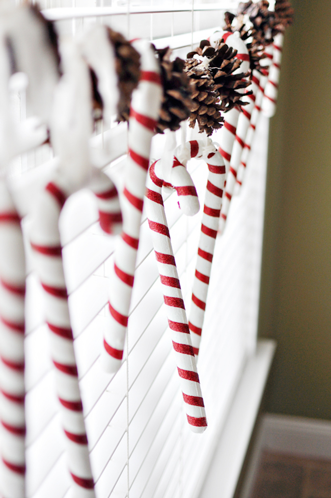 Candy canes and pinecones hung in a window