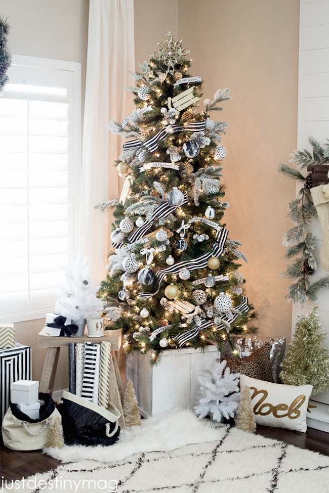 Christmas tree with gold ornaments plus black and white striped ribbon