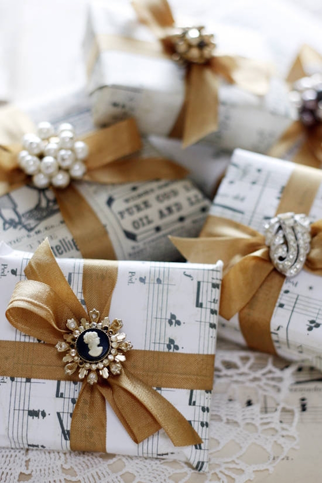 DIY wrapping paper using sheet music, gold ribbon, and jewelry pieces