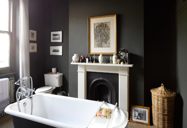 Dark walls and tub with a stunning black and white fireplace