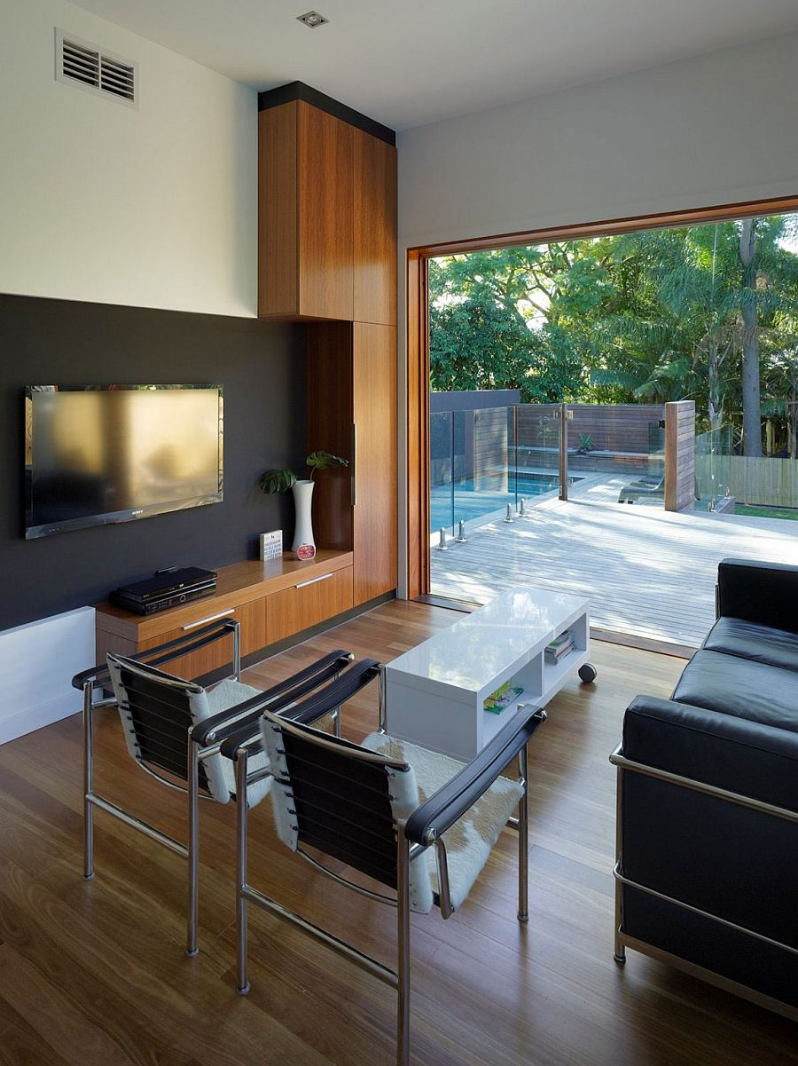 Living area of the modest family home in Australia overlooking the pool and deck