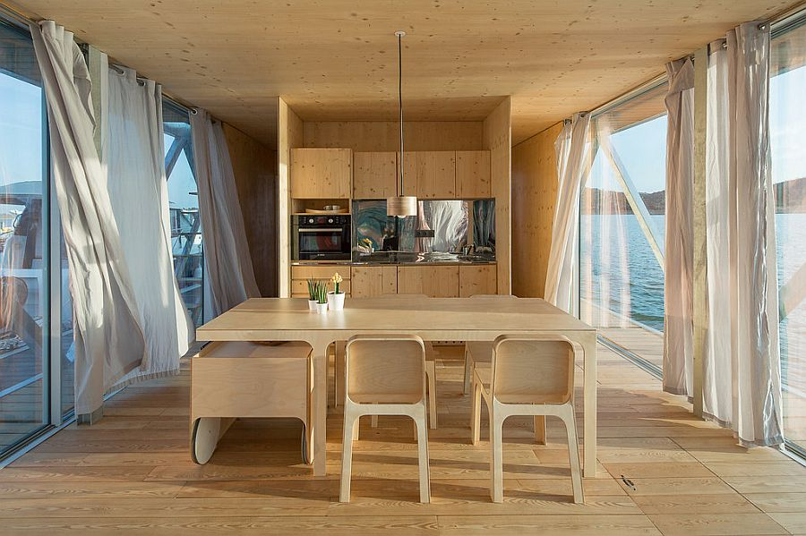 Open plan living area with dining space and kitchen inside the uber-cool floating house
