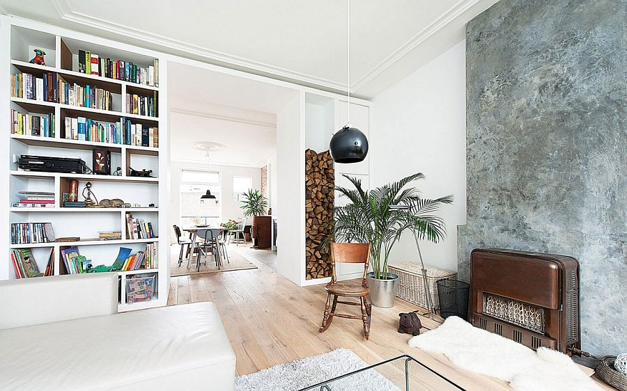 Stacked firewood and concrete fireplace add texture to the living room