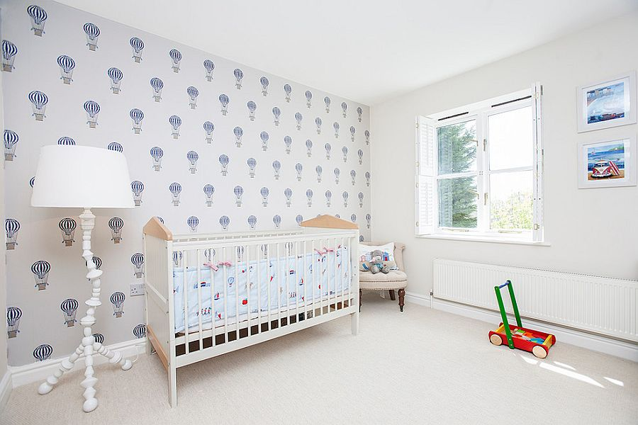 Beach style nursery in white with wallpaper that carries air balloon motif