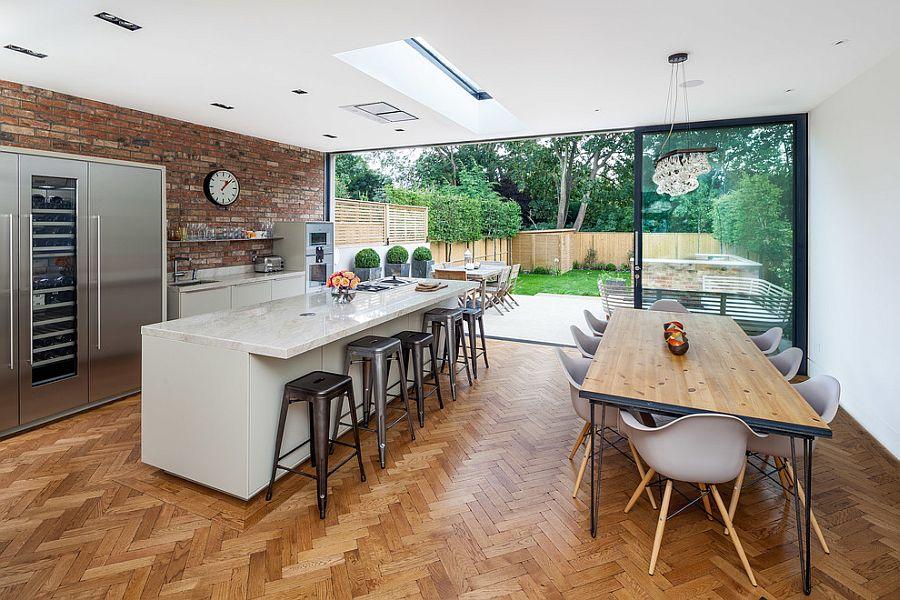 Herringbone pattern flooring and brick wall backsplash in the modern kitchen [Design: Concept 8 Architects]