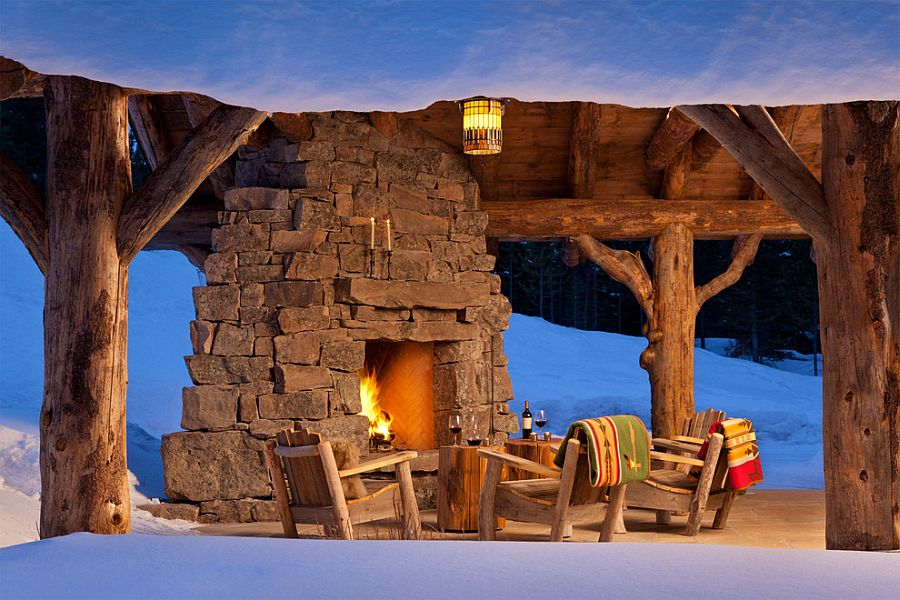 Stump side tables, wooden chairs and cozy stone fireplace make a magical patio at Spanish Peaks Cabin