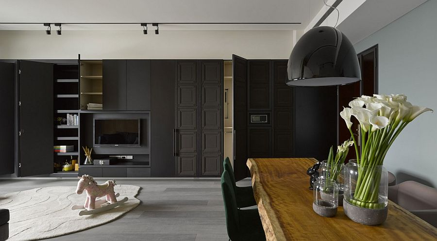 Smart cabinets in the living area blend into the dark backdrop seamlessly
