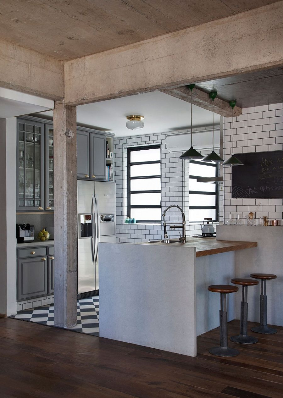 Gray cabinets and tiles separate the kitchen from the small living space