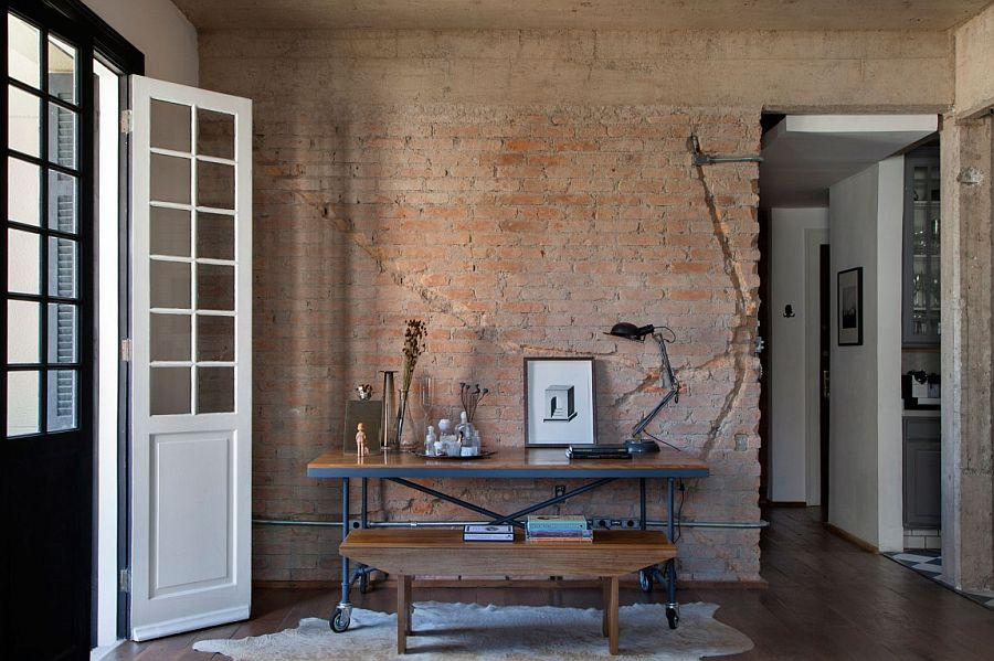 Home workspace with table on wheels and exposed brick wall